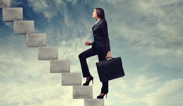 Mulher subindo escada corporativa