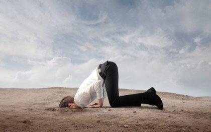 Homem com a cara enfiada na areia