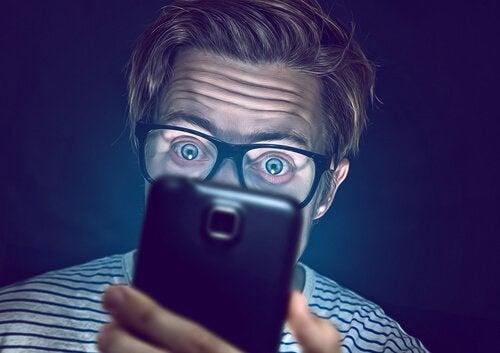 Homem usando celular no escuro