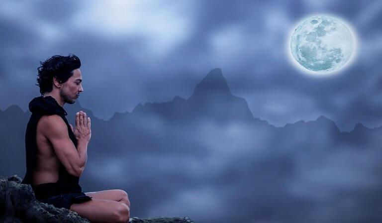 Homem meditando sob a luz do luar