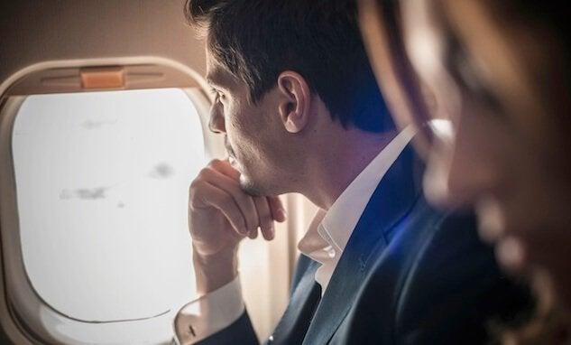 Homem olhando pela janela do avião