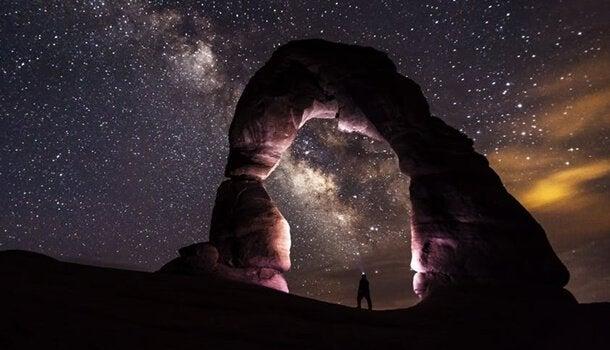 Homem em paisagem sob céu estrelado
