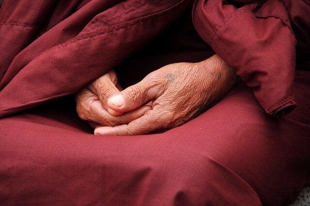 Mãos de monge idoso
