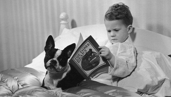 Criança lendo livro com seu cachorro
