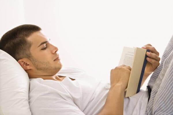 Homem lendo em sua cama