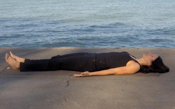 Mulher deitada no chão diante do mar