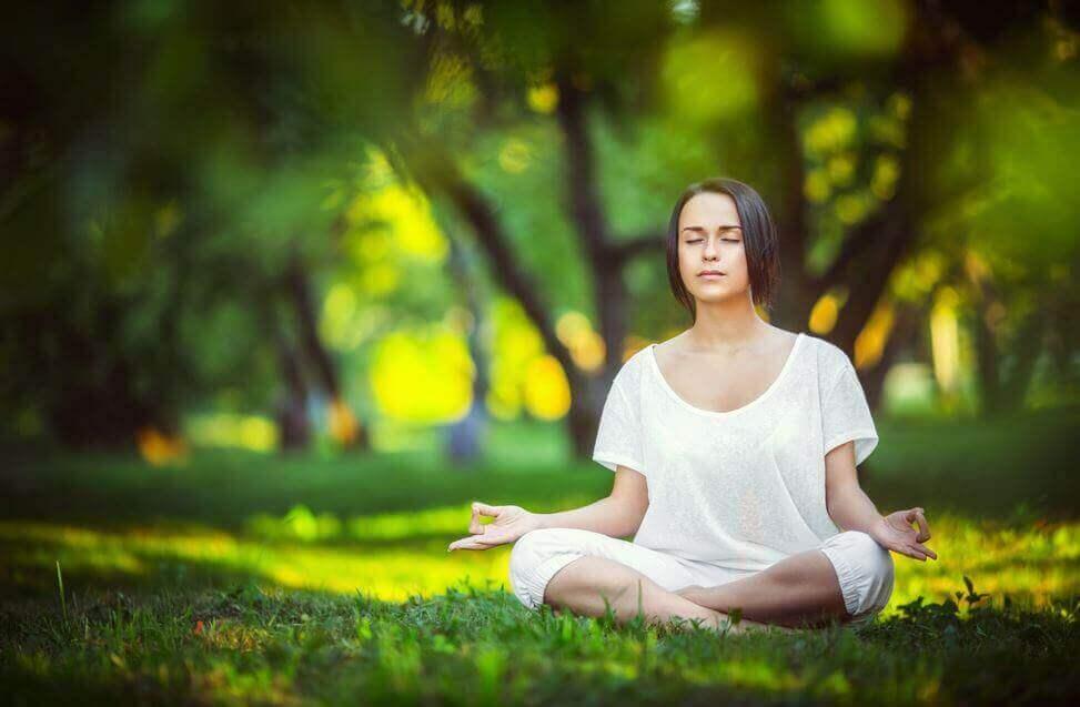 Mulher fazendo meditação no parque