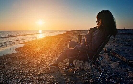 Mulher observando pôr do sol na praia
