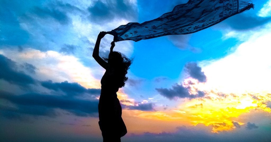Mulher com canga ao vento