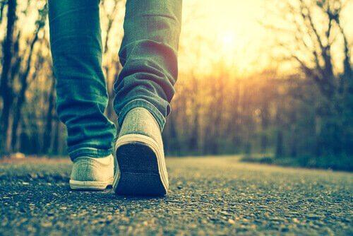 Pessoa caminhando em estrada vazia