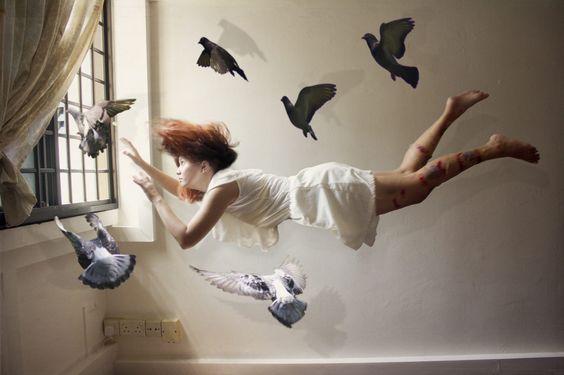 Mulher flutuando com pombos