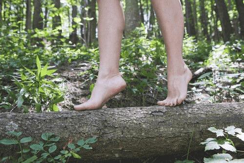 Pessoa passeando descalça em floresta