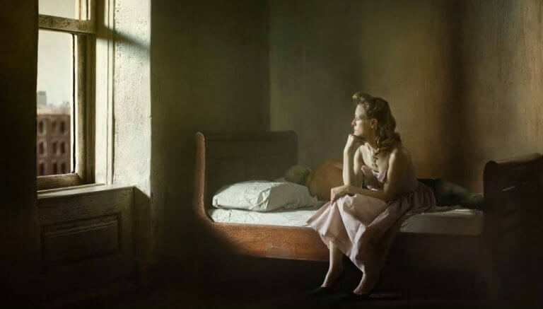 Mulher sentada na cama olhando pela janela