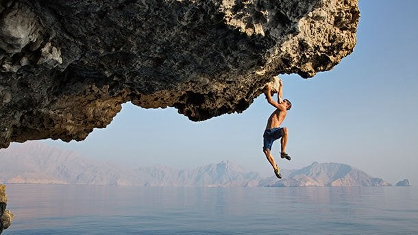 Homem fazendo escalada arriscada