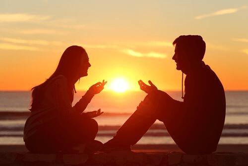 Casal conversando diante do pôr do sol