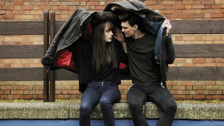 Casal se protegendo da chuva