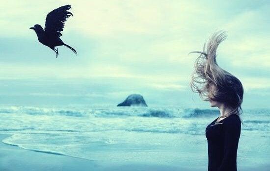 Mulher em praia diante de pássaro preto voando