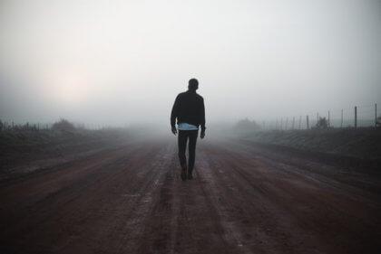 Homem caminhando em estrada deserta
