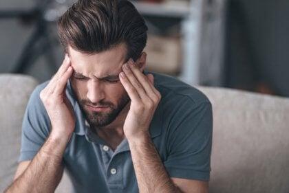 Homem sentindo dor de cabeça