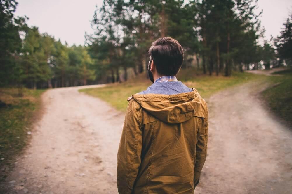 Homem tentando decidir entre dois caminhos