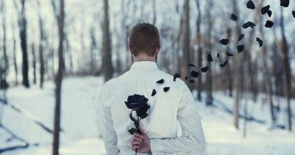 Homem escondendo flor preta com as pétalas voando