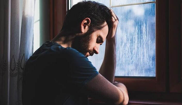Homem chateado diante de janela