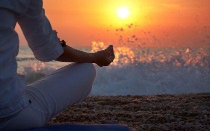 Mulher meditando diante do mar