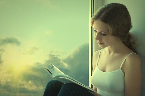 Mulher lendo livro na janela