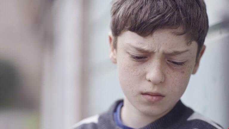 Menino triste por sofrer bullying na família