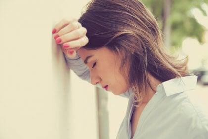 Mulher cansada com a cabeça na parede
