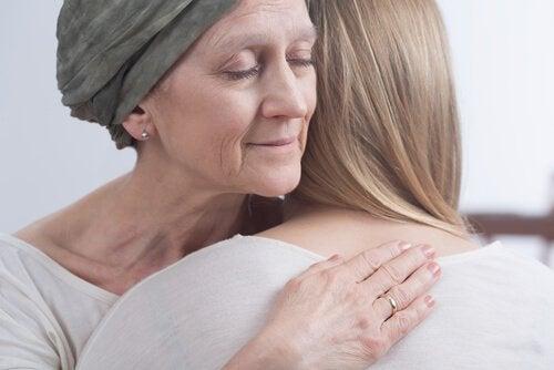 Mulher com câncer abraçando filha