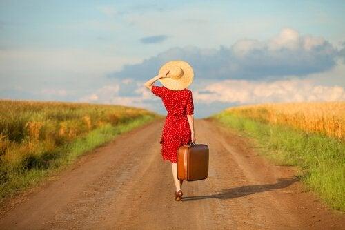 Mulher caminhando em estrada com mala