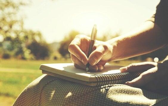 Pessoa escrevendo em caderno