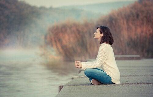 Mulher meditando diante de um lago