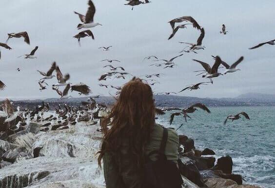 Mulher em meio a pássaros voando