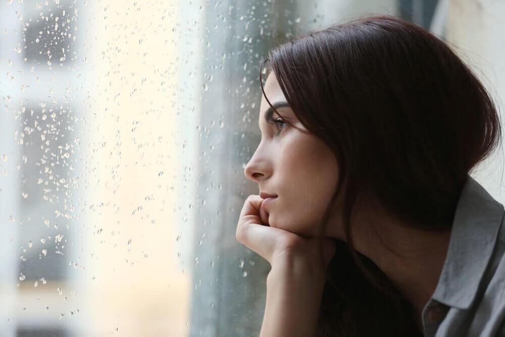 Mulher observando chuva na janela