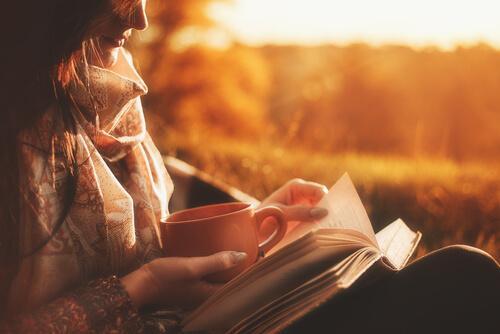 Mulher lendo livro com xícara de café
