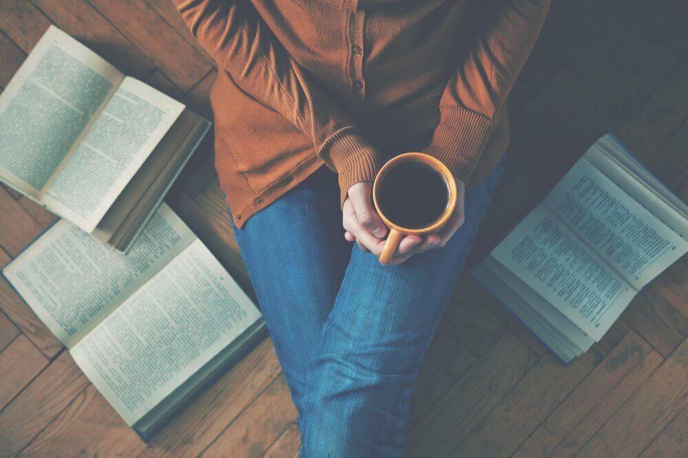 Mulher sentada em meio a livros abertos