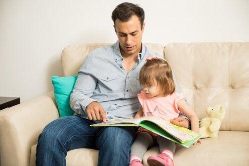 Pai lendo para filha pequena