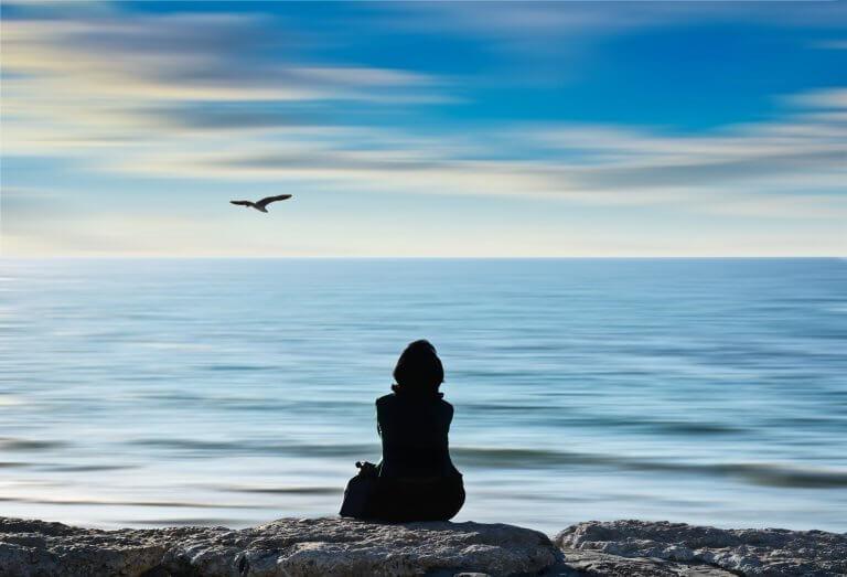 Mulher na praia observando pássaro
