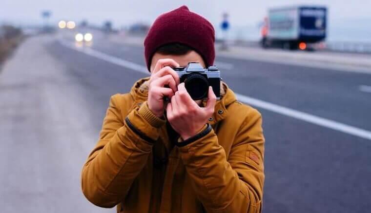 Homem tirando foto em estrada