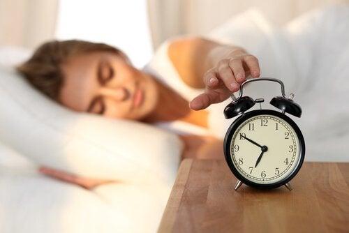 Mulher desligando despertador
