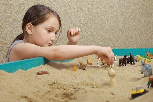 Menina brincando com brinquedos na areia