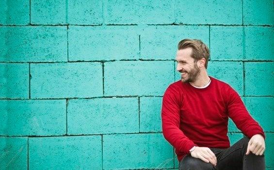 Homem diante de muro verde
