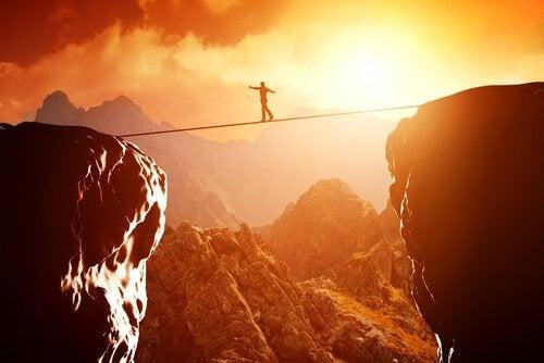 Pessoa cruzando montanhas em corda-bamba