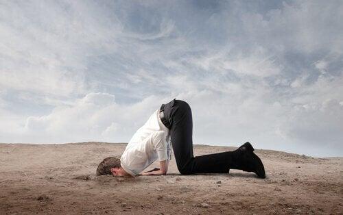 Homem com o rosto enfiado na areia