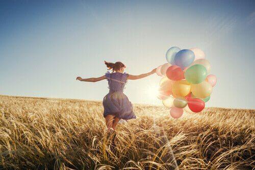 Mulher correndo com balões coloridos