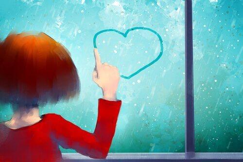 Menina desenhando coração em vidro