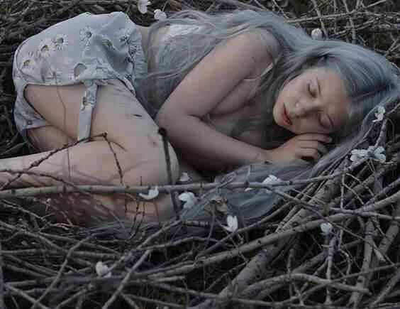 Mulher dormindo em ninho de galhos