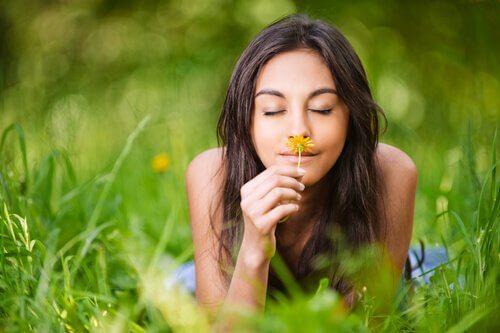 Mulher sentindo o aroma de uma flor